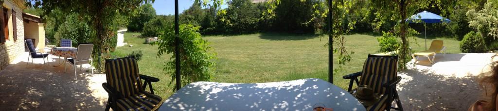 Blick von der schattigen Terrasse unter der Pergola in den Garten (Panorama-Aufnahme)